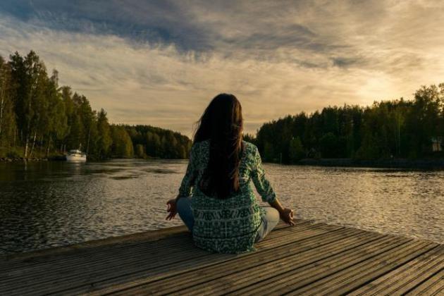 Jeune femme qui médite au bord d'un lac en fin de journée